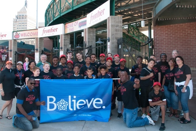 """Group photo with """"Believe"""" banner."""
